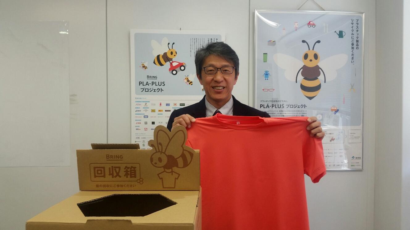 創業者で会長の岩元美智彦さん。再生したTシャツと、回収箱と
